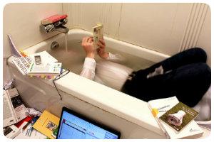 Photo d'un homme dans une baignoire en costard, entouré par son pc et des livres