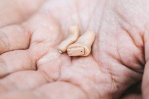 appareils auditifs dans une main